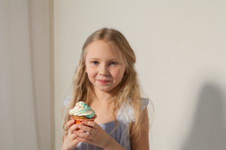 small girl in hand holds a sweet cupcake cake Banco de Imagens
