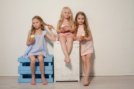 three girlfriends sisters eat sweet lollipop candy Archivio Fotografico
