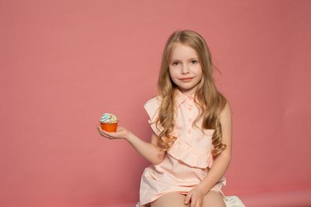 la pequeña niña en la mano sostiene un dulce pastel de magdalenas