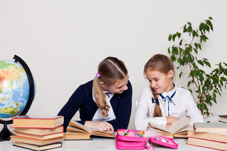 two schoolgirls girls in class at her desk with books notebooks