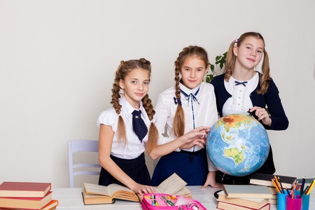 three schoolgirls girls learn world geography lesson on the map 版權商用圖片