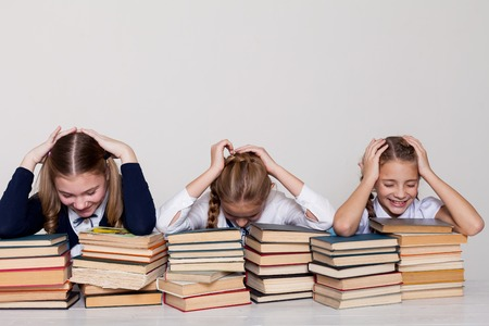 three girls schoolgirls at a desk with books on the lesson at school