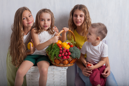 four children with fresh vegetables healthy food
