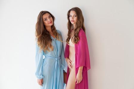Dos hermosas mujeres de moda en lencería juntos en paredes blancas