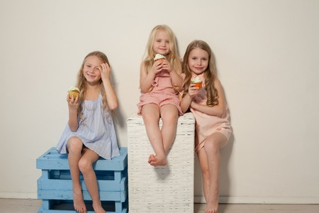 three little girls eat sweet cake with cream cupcake