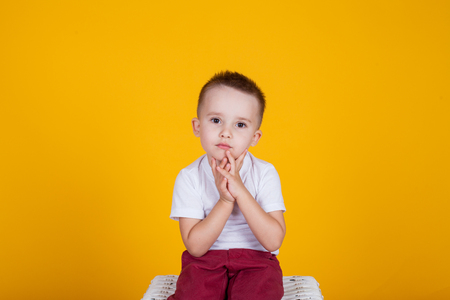 Portrait of a handsome boy, on a yellow background, and four years