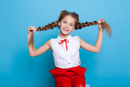 beautiful girl with braids with a red pencil on blue background Banque d'images - 114245846
