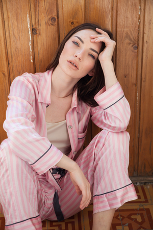 woman in pink Pajamas fashionable portrait bedroom