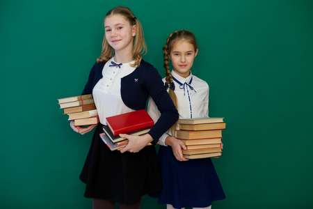 two girls schoolgirl is standing at the Blackboard with lesson books Imagens