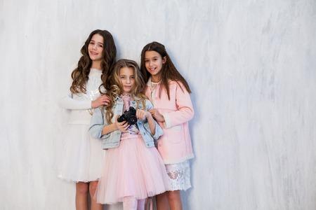 three fashionable girls school friend with a camera Stok Fotoğraf