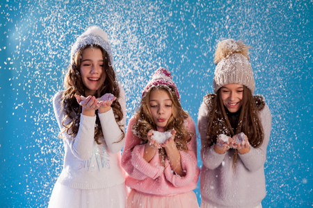 three fashionable girls in winter knitted hats snow winter Stok Fotoğraf