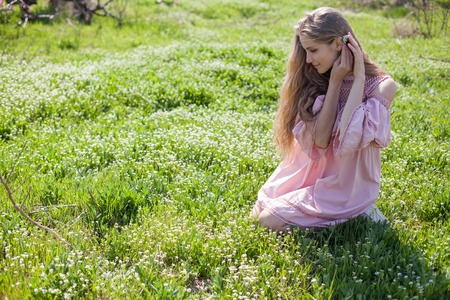 beautiful blonde woman collects spring color in the garden