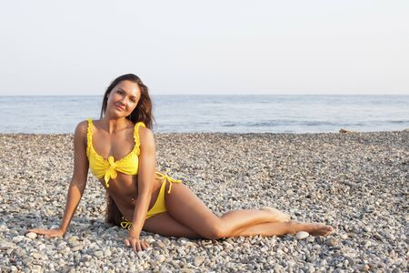 Beautiful woman with long hair in yellow swimsuit sunbathes on the beach
