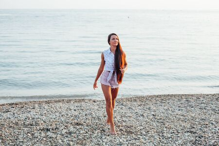 Beautiful woman with long hair walks on the beach