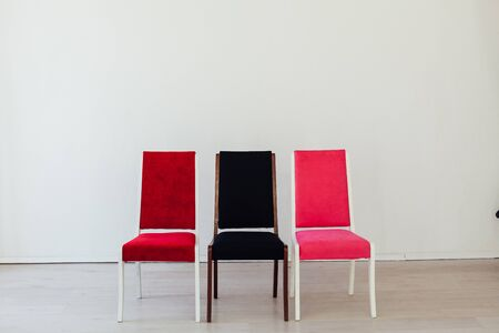 three chairs of red black and pink stand in the white room