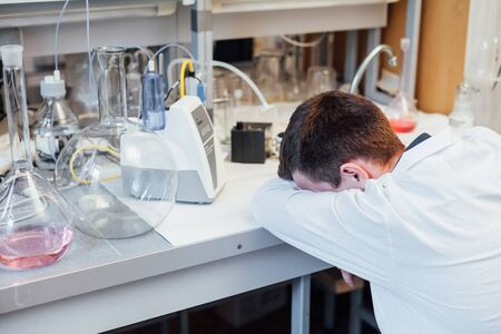 Male scientist tired of wanting to sleep after chemical experiments in lab