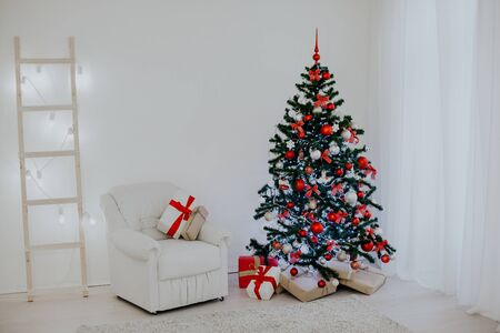 Christmas tree in a white room with a Christmas greeting gifts 2018