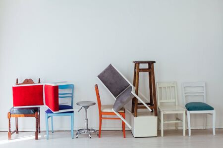 many different chairs stand in the white room moving