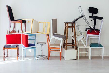 desorden de muchas sillas diferentes de pie en la sala blanca