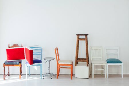 clutter of many different chairs standing in the white room Banco de Imagens