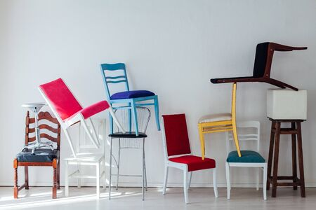 clutter of many different chairs standing in the white room Stock fotó