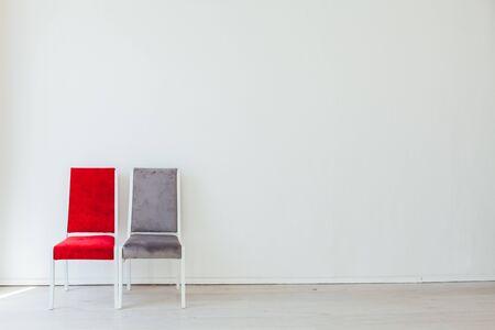Dos sillas viejas en el interior de una habitación blanca vacía.