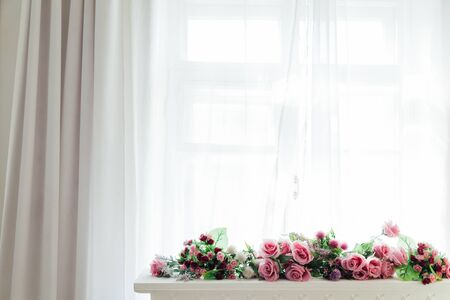flowers lie by the window in the white room