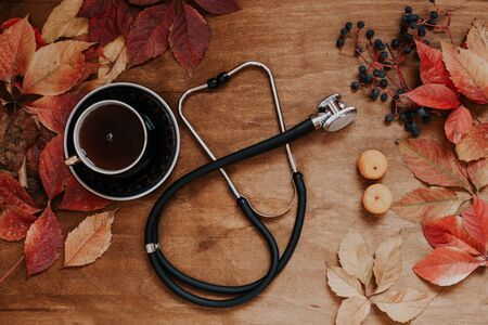 autumn fruits red berries yellow leaves stethoscope tea Stock Photo