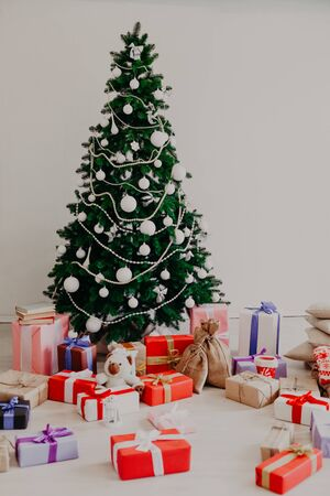 Christmas tree with Christmas gifts in white room winter Reklamní fotografie