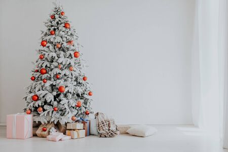 Christmas tree in a white room with gifts