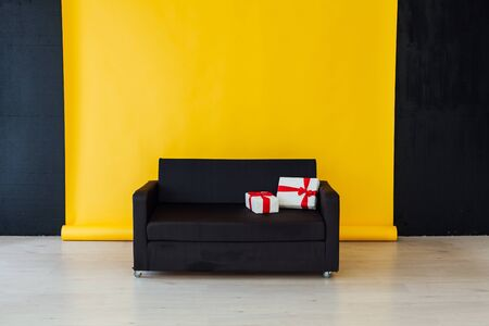 black office sofa with red gifts in the interior of the room with a yellow background Stockfoto