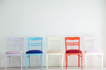 White room with colorful chairs blue yellow red blue purple pink