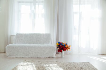 sofa with flowers in the interior of the white room of the house