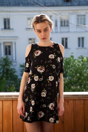 Porter beautiful fashionable blonde woman in a dress with flowers