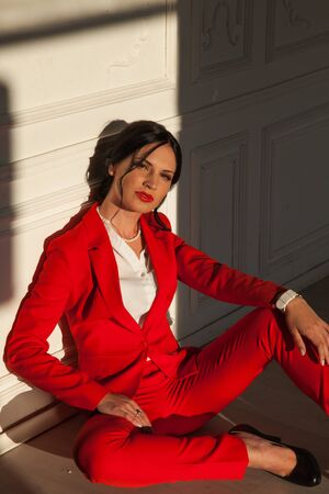 portrait of a beautiful woman in a red business suit in the office Archivio Fotografico - 132405147