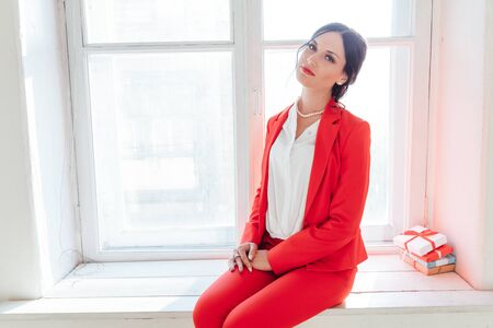 portrait of a beautiful woman in a red business suit in the office Archivio Fotografico - 132405152
