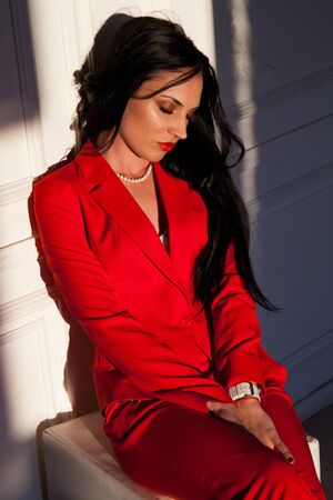 portrait of a beautiful woman in a red business suit in the office Archivio Fotografico - 132405175