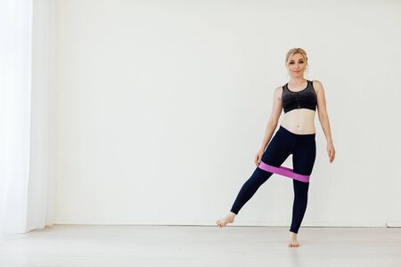 Blonde woman sports with fitness gum white Stock Photo