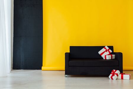 black sofa with feasting gifts in the interior of the room with a yellow background