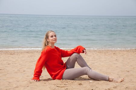 Beautiful blonde woman sits on the sand on an empty beach by the sea
