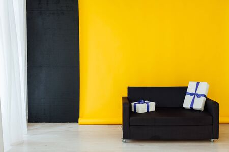 sofa with a gift in the interior of the room with a yellow background