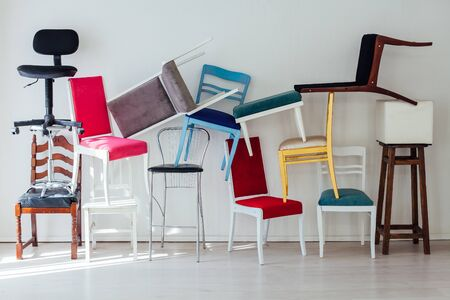 lots of different multicolored chairs in the interior of the white room