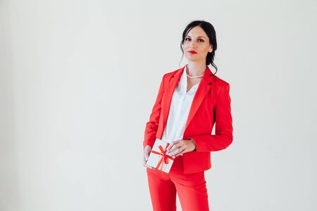 Portrait of a brunette woman in a red business suit with a gift