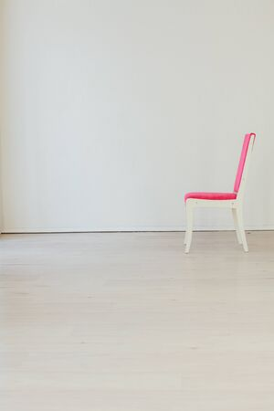one pink chair in an empty white interior room