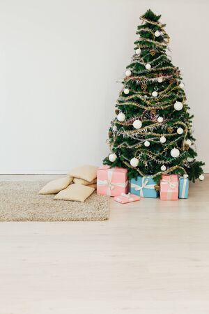 Christmas tree with gifts for the new year in the interior of the room