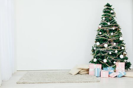 Christmas tree with gifts for the new year in the interior of the white room