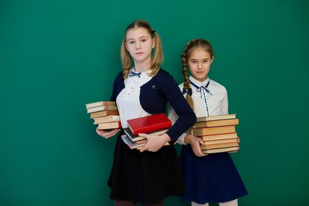 two schoolgirl girls with books in class education Фото со стока