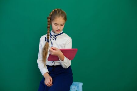 girl with an internet tablet in a lesson at the board at school