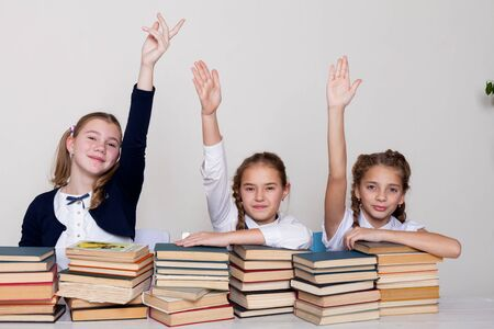 thre girls with books in class at a desk at school