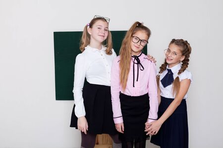 three schoolgirl girls standing at the school board in class 스톡 콘텐츠